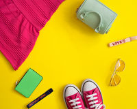 Vintage girly fashion items. In a flat lay composition over yellow background stock photography