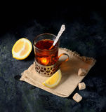 Vintage glass-holder on knitted napkin with cup of tea with sliced lemon and sugar cubes over old metal table. Royalty Free Stock Photography