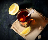 Vintage glass-holder on knitted napkin with cup of tea with sliced lemon and sugar cubes over old metal table. Royalty Free Stock Photos