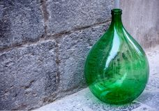 Vintage glass wine bottle. Vintage large green glass wine bottle of round shape on the sidewalk stock image