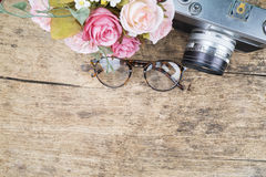 Vintage glasses and camera on wooden background. Royalty Free Stock Images