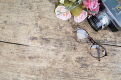 Vintage glasses and camera on wooden background. Stock Photos