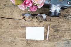 Vintage glasses and camera on wooden background. Stock Image