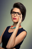 Vintage glasses and hairstyle. Trendy hairstyle and glasses for a young vintage woman, studio shot Royalty Free Stock Photos