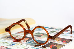 Vintage glasses. Horn-rimmed glasses and an old stamp album Stock Images