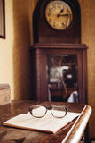 Vintage glasses on old book, old clock in background Royalty Free Stock Photo
