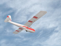 Vintage glider in the sky. Vintage red and white flying glider against a blue sky with thin clouds.  Suitable for background Royalty Free Stock Photo