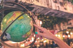 Woman hand on vintage globe close up in the antique store on Bali island, Indonesia. royalty free stock photos