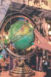 Woman hand on vintage globe close up in the antique store on Bali island, Indonesia. stock photos