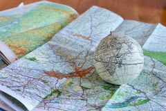 A vintage globe on a table with maps under it and a wooden floor in the background Stock Photos