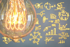 Vintage glowing light bulb with business graph Stock Images