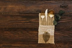 Vintage gold cutlery with eucalyptus an old wooden background. stock photos