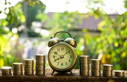 Vintage golden alarm clock with stacks of coin. Time and money for financial concept. Copy space. Vintage golden alarm clock with stacks of coin. Time and money stock image