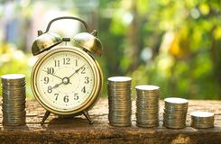 Vintage golden alarm clock with stacks of coin. Time and money for financial concept. Copy space royalty free stock images