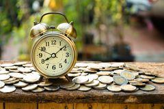 Vintage golden alarm clock with stacks of coin. Time and money for financial concept. Copy space stock photos