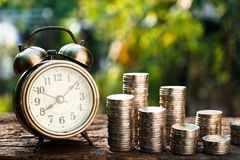 Vintage golden alarm clock with stacks of coin. Time and money for financial concept. Copy space royalty free stock image
