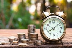 Vintage golden alarm clock with stacks of coin. Time and money for financial concept. Copy space stock image