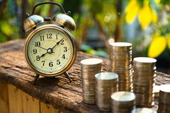 Vintage golden alarm clock with stacks of coin. Time and money for financial concept. Copy space stock photography