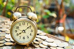 Vintage golden alarm clock with stacks of coin. Time and money for financial concept. Copy space royalty free stock photo