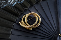 Vintage golden brooch on a hand fan Royalty Free Stock Photos
