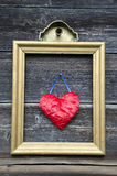 Vintage golden picture frame with red heart on wall Stock Image