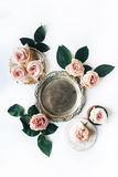 Vintage golden tray, retro plate and pink rose flower with green leaves on white background Stock Photo