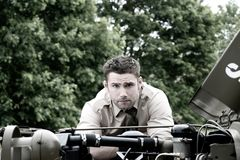 Handsome American WWII GI Army officer in uniform and rolled up sleeves next to broken down Willy Jeep. Vintage good looking, attractive man, American Soldier royalty free stock photography