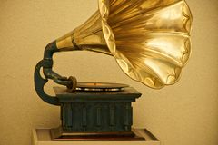 Vintage gramophone in a golden hue. Old retro music. Vintage items and old technology royalty free stock photography