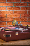 Vintage gramophone on table and background of brickwall royalty free stock photo