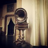 Vintage gramophone on a theatre stage. Retro gramophone from theatre props. Stage curtain on background Royalty Free Stock Photo