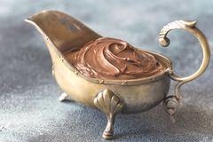 Vintage gravy boat with chocolate cream. On the wooden table Royalty Free Stock Photos
