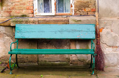 Vintage green bench and broom. In front of an old house Stock Photos