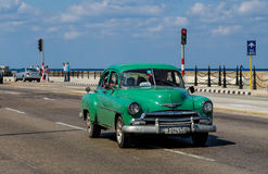Vintage green car. Vintage american car and tourists on Malecon boulevard in Havana, Cuba Royalty Free Stock Images