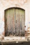 Vintage green closed damaged door Stock Photos