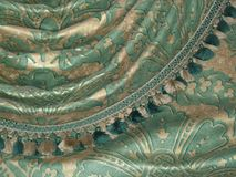 Vintage green and gold tassled velvet curtains background close-up. A close up of a section of vintage green and gold velvet curtains drapes with tassled edges Royalty Free Stock Image