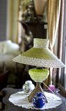 A Vintage Green Lamp With A Lace Edged Shade. A vintage green glass lamp with a lace edged shade sits on an old occasional table between two pieces of porcelain Stock Photography