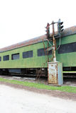 Vintage green railway passenger car with partially boarded windows and old railway track light. Vertical aspect Stock Images