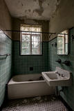 Vintage Green Tiled Bathroom with Fixtures - Abandoned Mansion stock photo