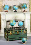Vintage green travel chest with brass fittings. Vintage green chest or trunk with brass fittings displayed with a collection of old world globes in front of a Royalty Free Stock Images