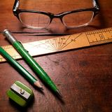 Vintage green writing utensils, ruler and spectacles. Antique desk surface with green pencil, vintage bakelite sharpener, vintage green mechanical pencil, ruler Royalty Free Stock Photo