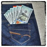 Vintage grunge American money is in the pocket of blue jeans. Stock Photography