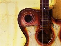 Vintage grunge background with guitar. On wall Stock Images