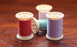 Vintage grunge colorful thread spool on wooden table Royalty Free Stock Images