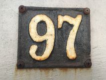 Vintage grunge square metal rusty plate of number of street address with number Stock Images