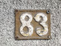 Vintage grunge square metal rusty plate of number of street address with number Royalty Free Stock Photography