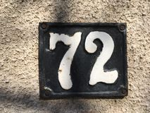 Vintage grunge square metal rusty plate of number of street address with number Stock Photo