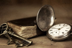 Vintage Grunge Still Life. With pocket watch, and old book and brass keys Stock Photos