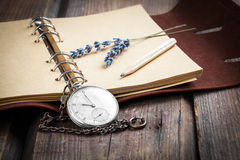 Vintage grunge still life with pocket watch. Lavender flower and old book stock photo