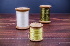 Vintage grunge three wooden thread spool with needle Royalty Free Stock Photo