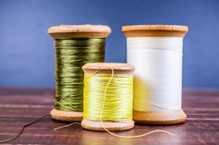 Vintage grunge three wooden threads spools Royalty Free Stock Image